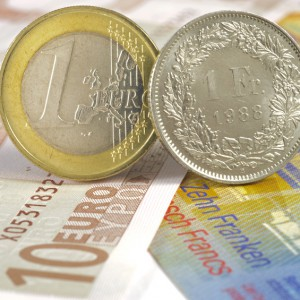 euro and swiss franc coin on banknotes
