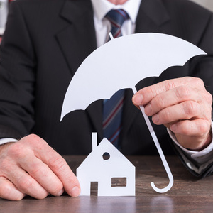 61684177 - house protected with an umbrella by an insurer - insurance concept